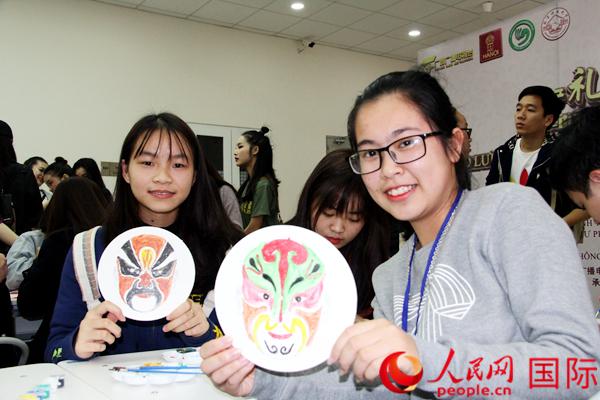 越南大学生展示脸谱作品。